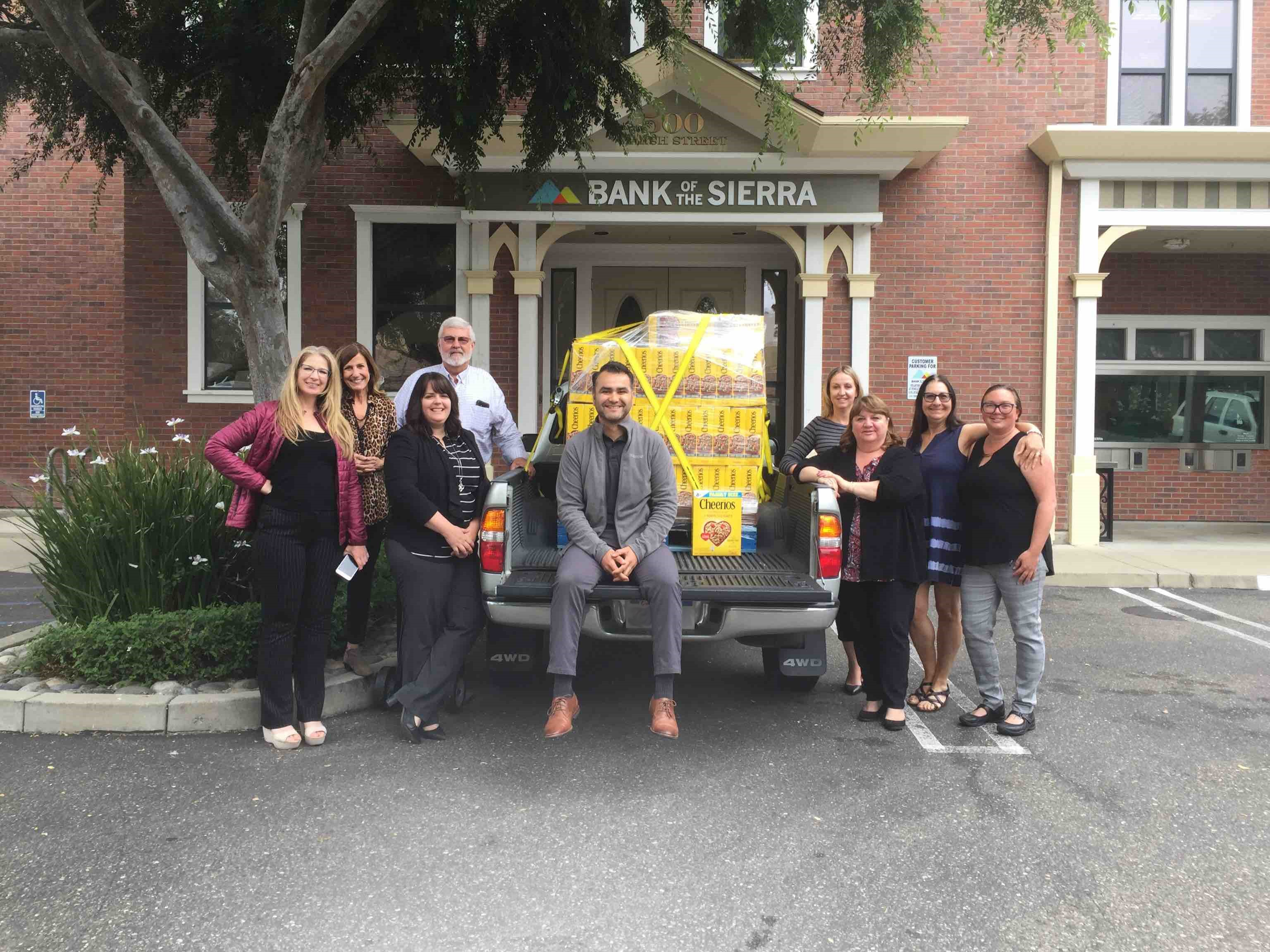 Bank of the Sierra SLO County employees stand next to a pick-up truck full of $600 worth of Cheerios.